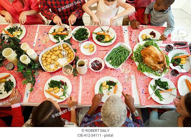 Overhead view family eating Christmas dinner