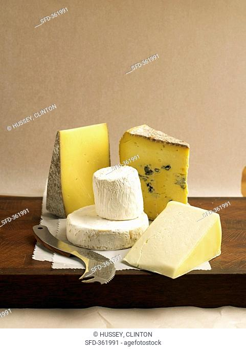 Various French and Italian cheeses with knife on a board