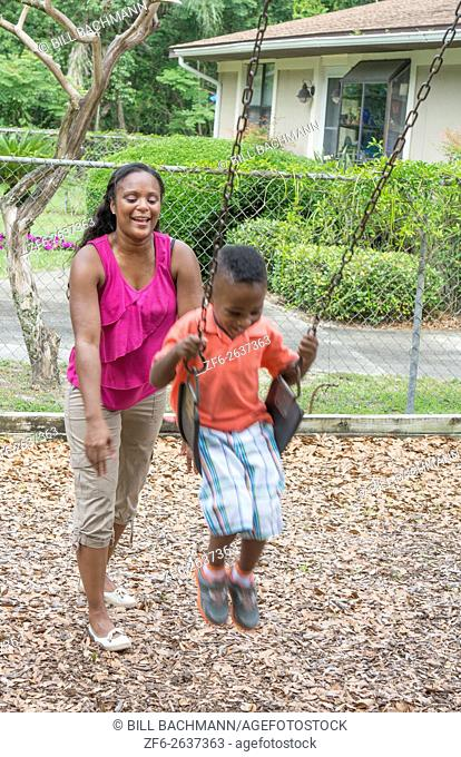 Black single mother swinging her 3 year old son on swings at park having fun together MR-7 MR -10 Model released