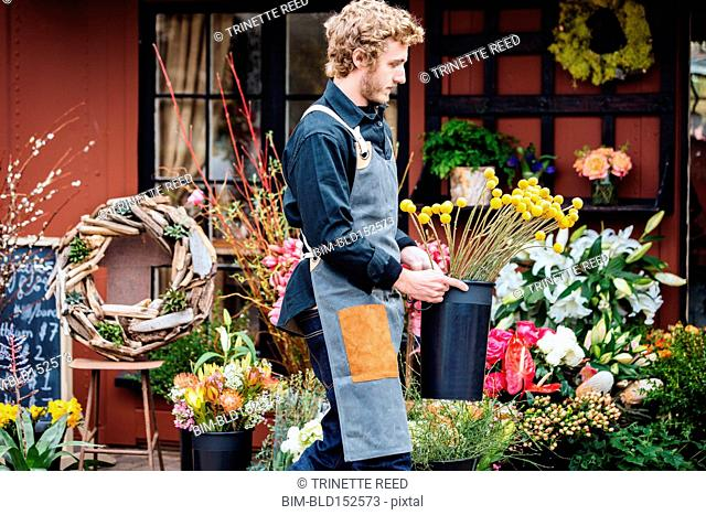 Caucasian florist carrying flowers outside shop