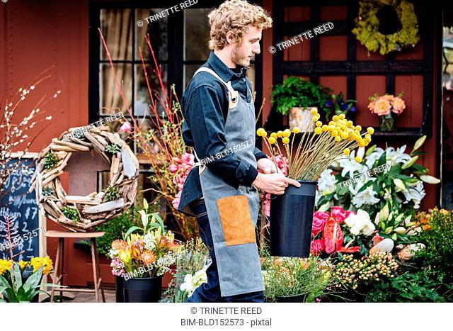 Caucasian florist carrying flowers outside shop