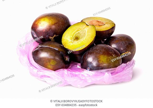 Whole and half violet plums in plastic bag isolated on white background