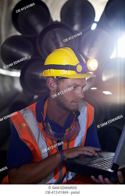 Worker using laptop in tunnel