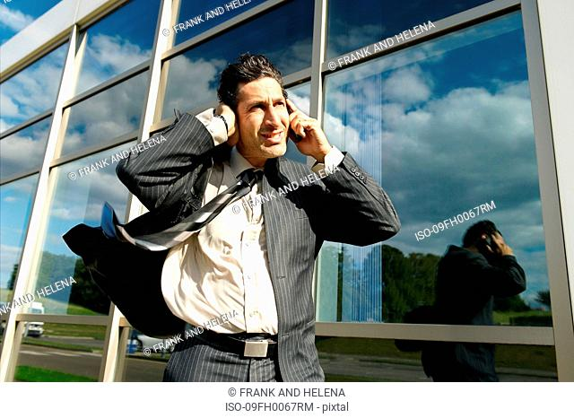 Business man with phone in wind