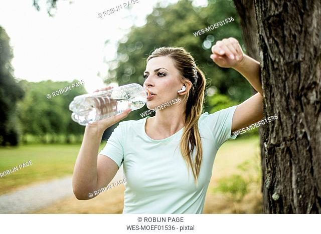 Sportive young woman leaning against a tree in a park drinking from bottle
