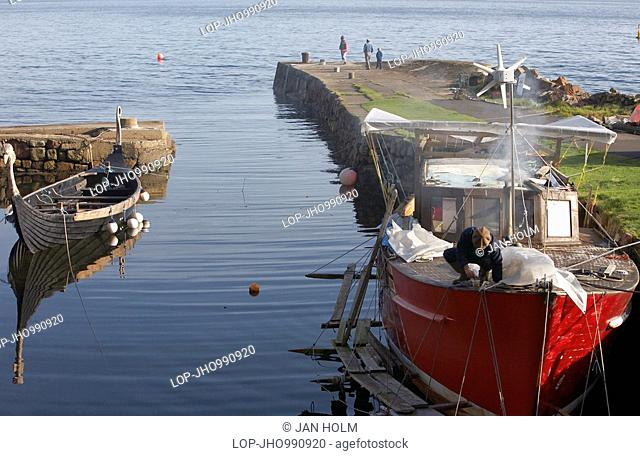 Scotland, North Ayrshire, Corrie, A fishing boat undergoing repair and replica Viking boat in Corrie Harbour on the Isle of Arran
