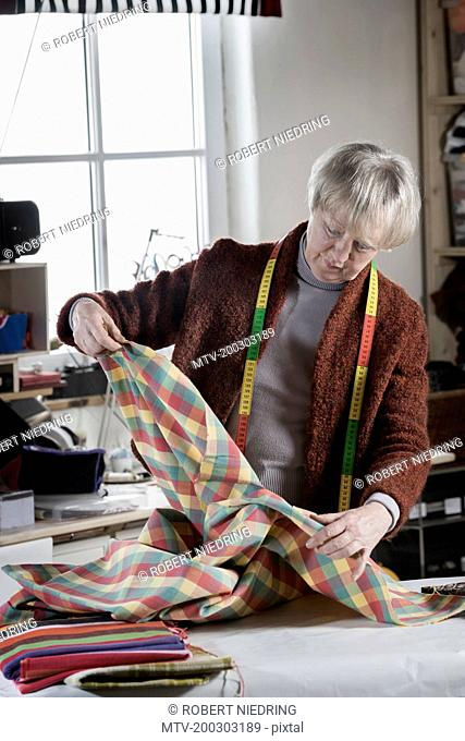 Senior female fashion designer checking fabric in workshop, Bavaria, Germany