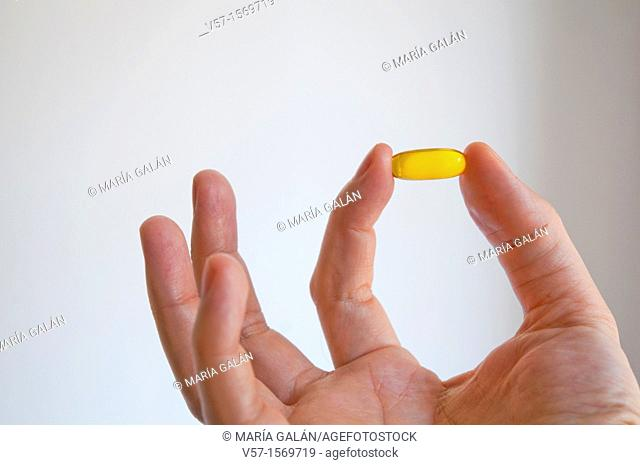 Man's hand holding a primrose pill. Close view