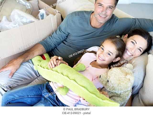 Portrait of smiling family with stuffed animals on sofa