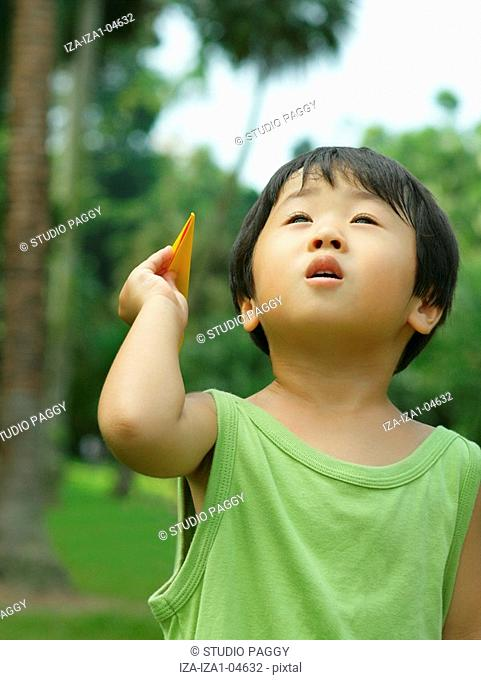 Close-up of a boy holding a paper airplane