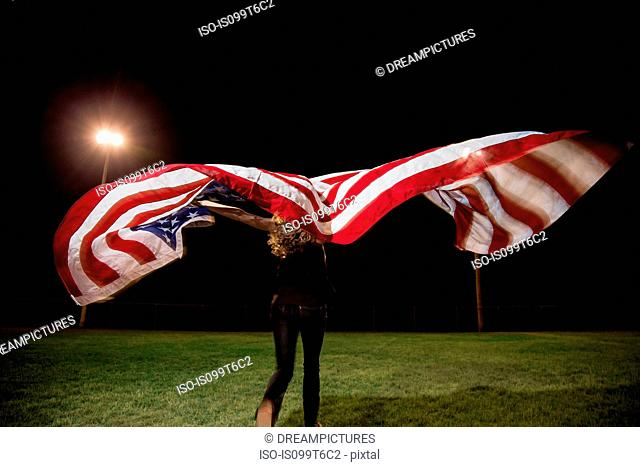 Girl holding american flag at night
