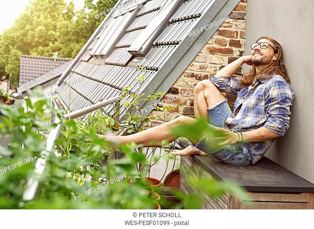 Happy young man sitting on his balcony, relaxing