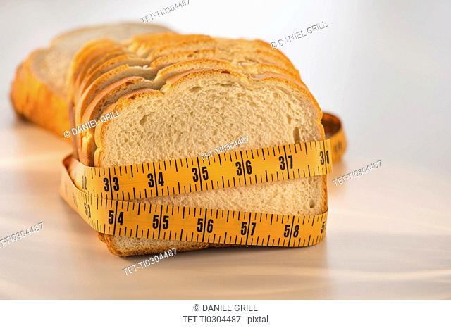 Studio Shot of measuring tape wrapped around slices of bread