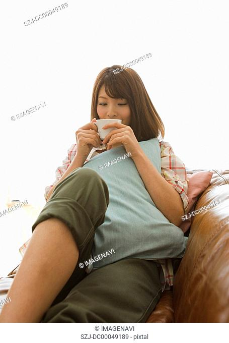 Middle-aged woman drinking a cup of coffee on a sofa