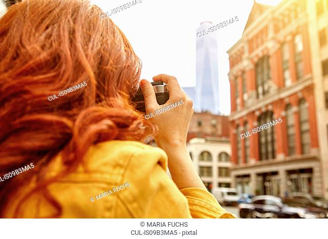 Young female tourist with long red hair photographing One World Trade Centre, Manhattan, New York, USA