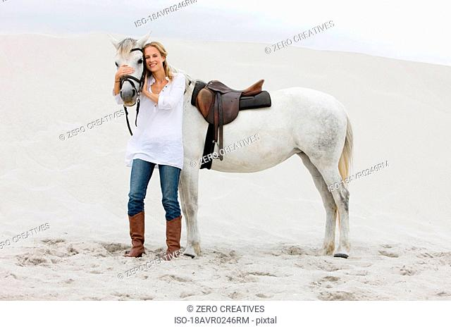 Blonde woman with horse on the beach