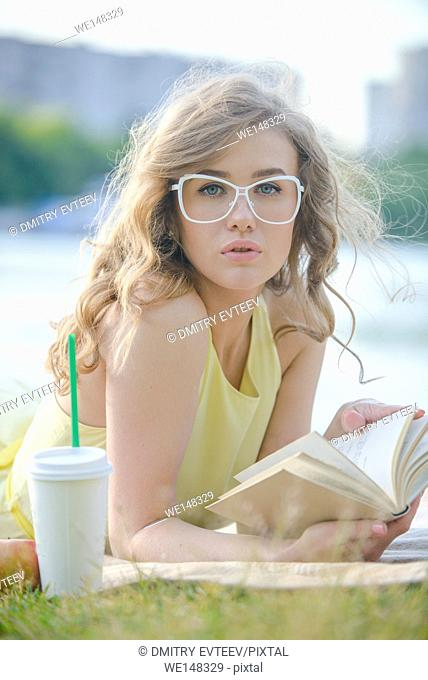 Romantic girl with book in citypark on river shore