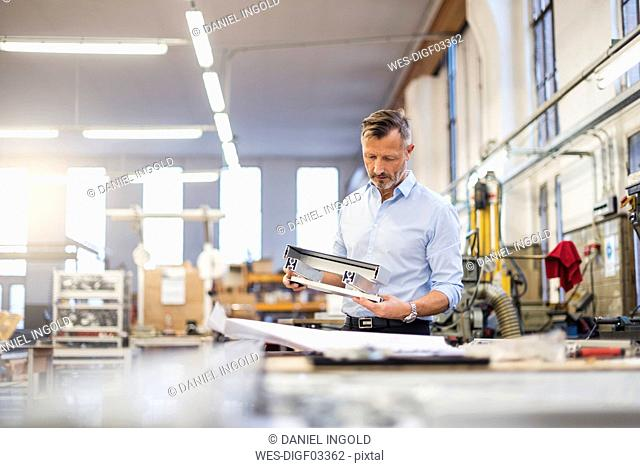 Mature businessman in factory examining component