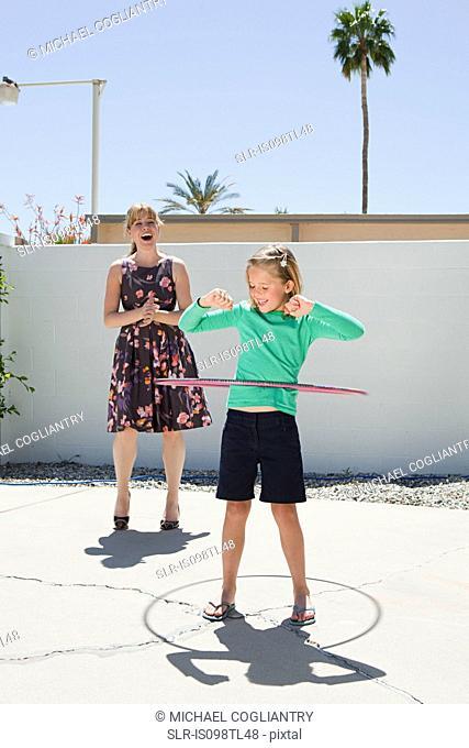 Mother watching daughter with hoola hoop