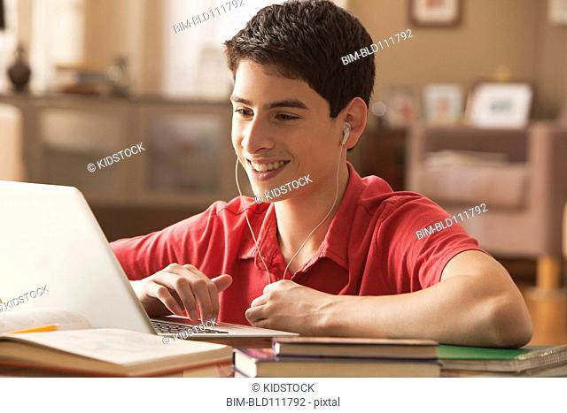 Hispanic boy using laptop at desk