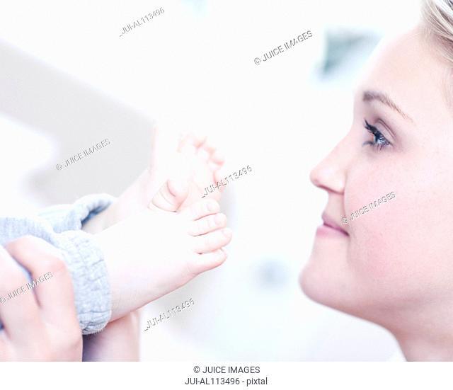 Teenage girl touching baby's feet