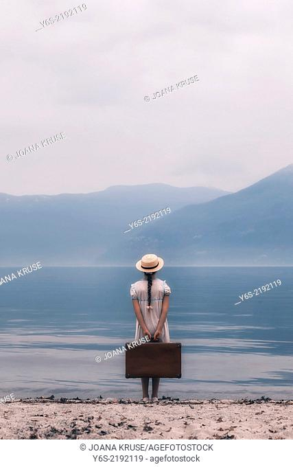 a girl at a lake with a suitcase