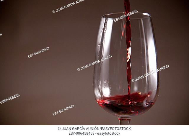 Glass with red wine poured on a cup. Isolated over dark background