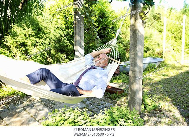 Businessman relaxing in hammock in a garden