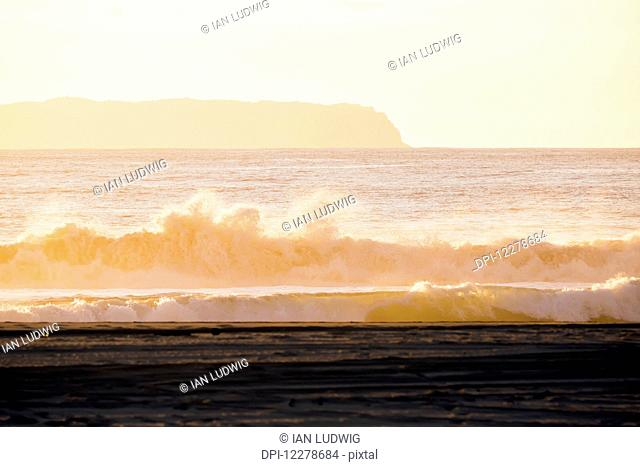 Golden surf visible from Barking Sands Beach in Kekaha with Niihau visible in the distance; Kekaha, Kauai, Hawaii, United States of America