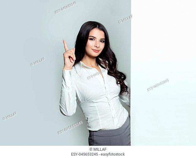 Business woman pointing up and holding white empty banner background with copy space for text. Young friendly woman, advertising marketing and product placement...