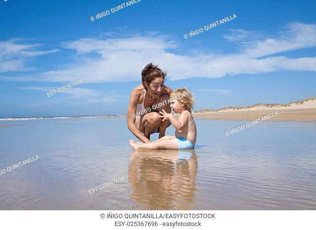 summer family of two years old blonde baby with blue swimsuit sitting on water with brunette woman mother in white bikini squatting at sea shore beach sand in...