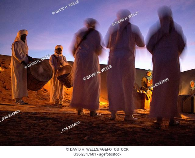 People relaxing on desert at night listening to local Gnawan musicians in Erg Chebbi, Morocco
