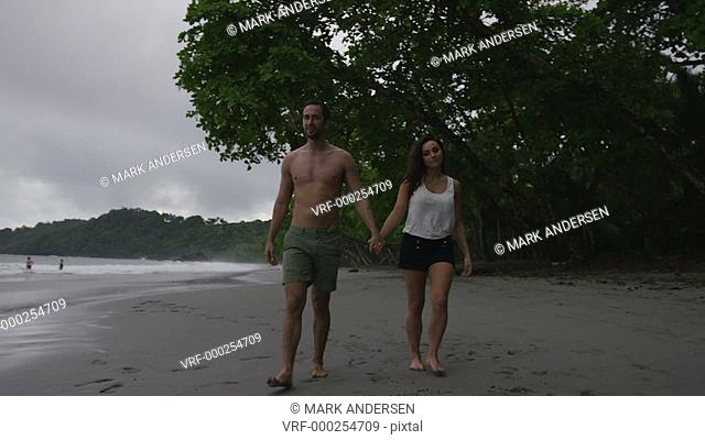 Slow motion tracking wide shot of man carrying girlfriend to ocean on beach / Manuel Antonio, Costa Rica