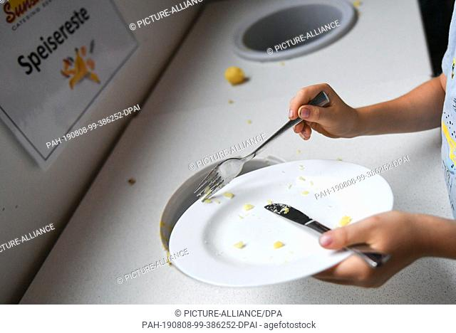 07 August 2019, Berlin: A student throws food scraps into a container provided. Photo: Jens Kalaene/dpa-Zentralbild/ZB. - Berlin/Berlin/Germany