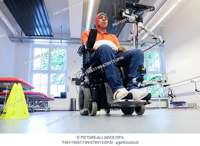 17 June 2019, North Rhine-Westphalia, Bochum: Sarshar Manoucheher, a paraplegic patient, uses a brain-computer interface to control his wheelchair with thought...