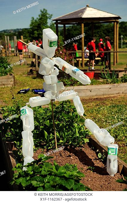 A scarecrow made from recycled plastic milk bottles in a primary school garden, Wales UK