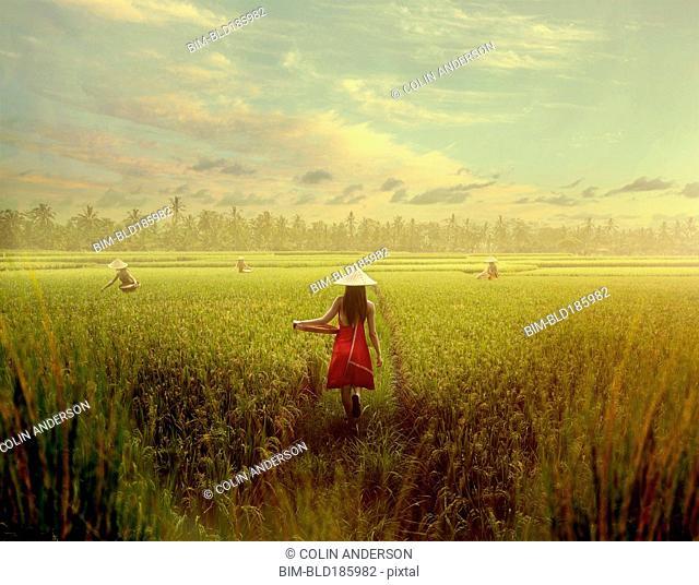 Pacific Islander woman walking in rice field