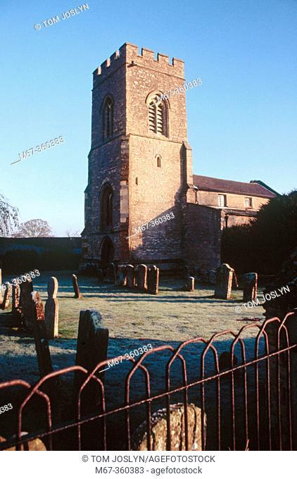 Church and graveyard in frost, Stoke Goldington in morning sunlight. Buckinghamshire, England, UK