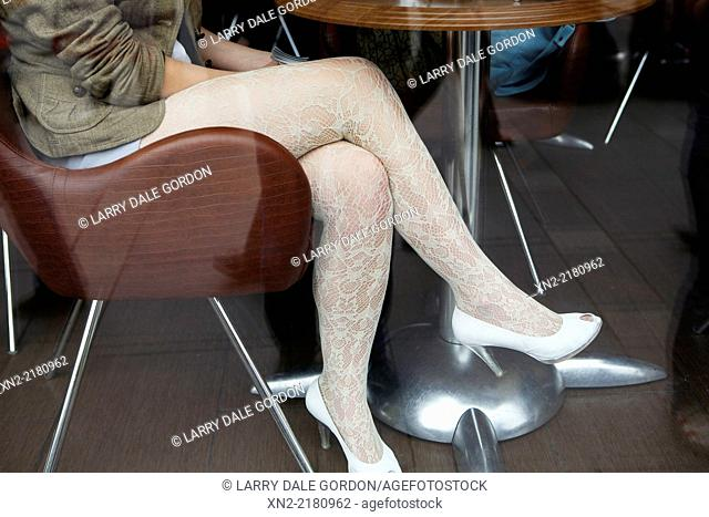 A young woman wears lace stockings in a cafe in Moscow, Russia