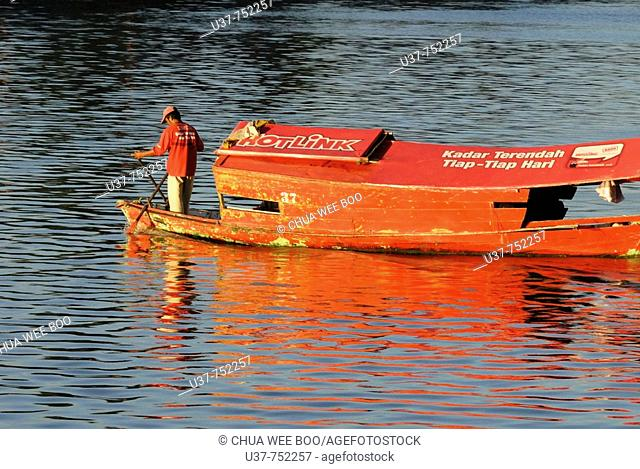 telecommunication advertisement on small wooden boat. (Sampan in Malay's words) which passengers across the Sarawak river everyday