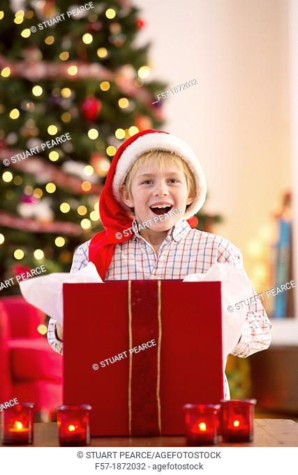 Young boy opening a Christmas present on Christmas day