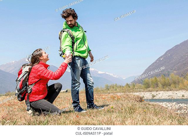 Young female hiker handing water bottle to boyfriend, Vogogna, Verbania, Piemonte, Italy