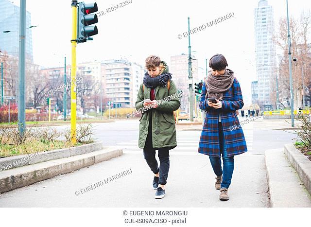 Two sisters walking along street, using smartphones