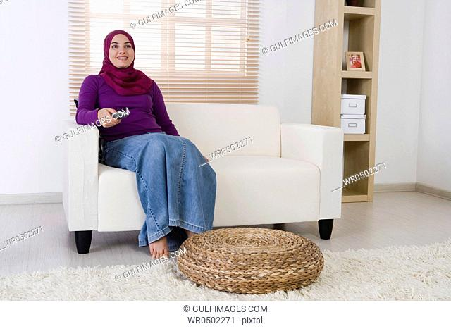 Woman holding the television remote control