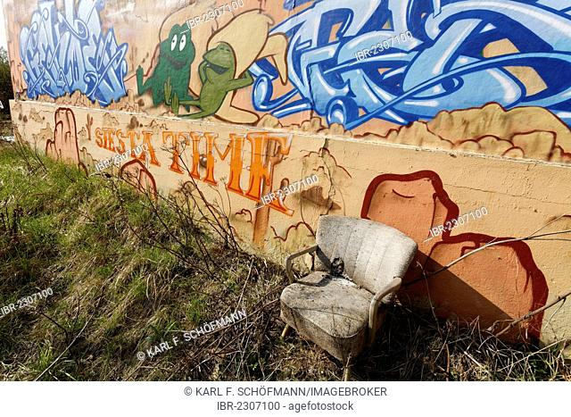 Siesta seat on a brownfield site, tattered armchair, graffiti wall, disused switching yard station, Duisburg-Wedau, Ruhr Area, North Rhine-Westphalia, Germany