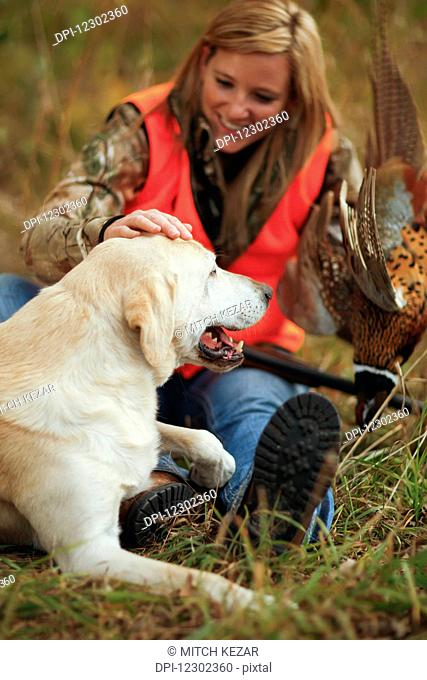 Woman Pheasant Hunter Relaxes With Lab After Hunt