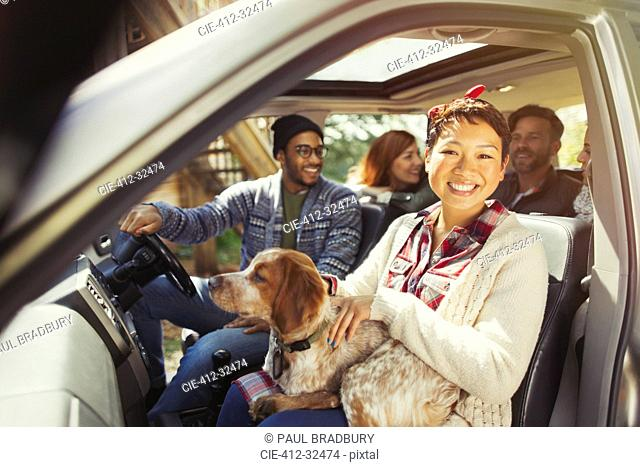 Portrait smiling woman with dog on lap in car with friends