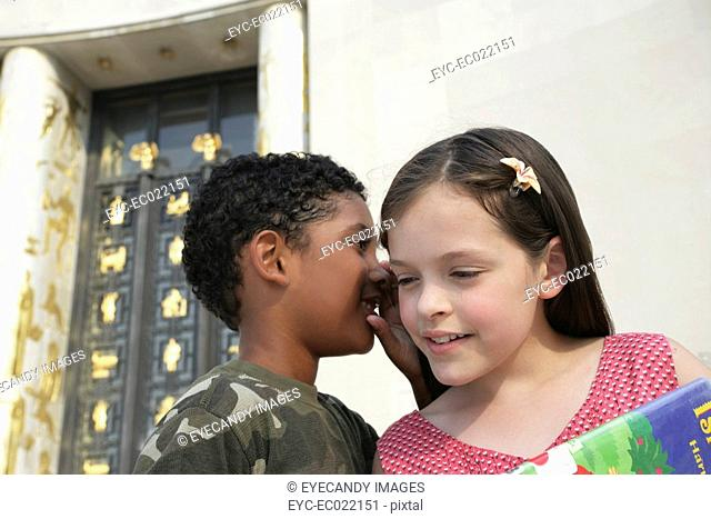 two kids, boy and girl with school books whispering