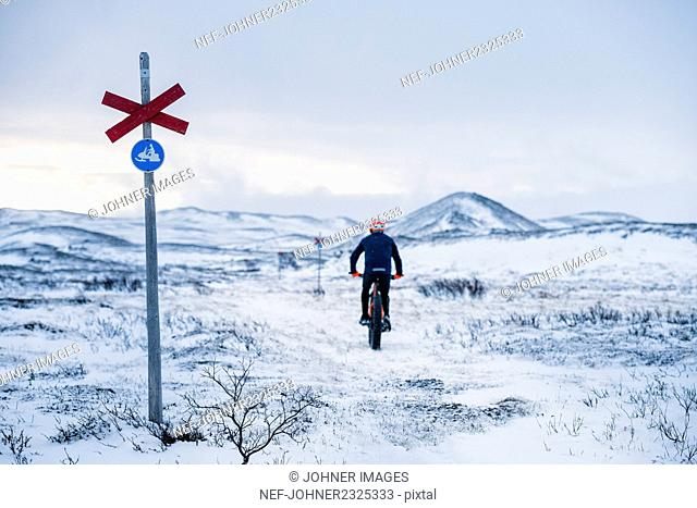 Man cycling in snow