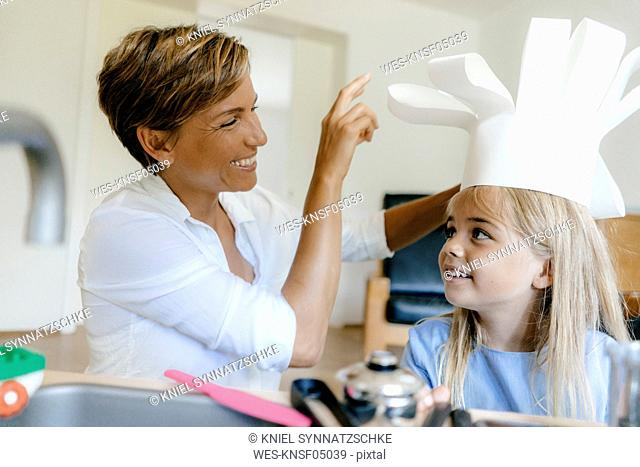 Happy mother and daughter playing at home putting on chef's hat